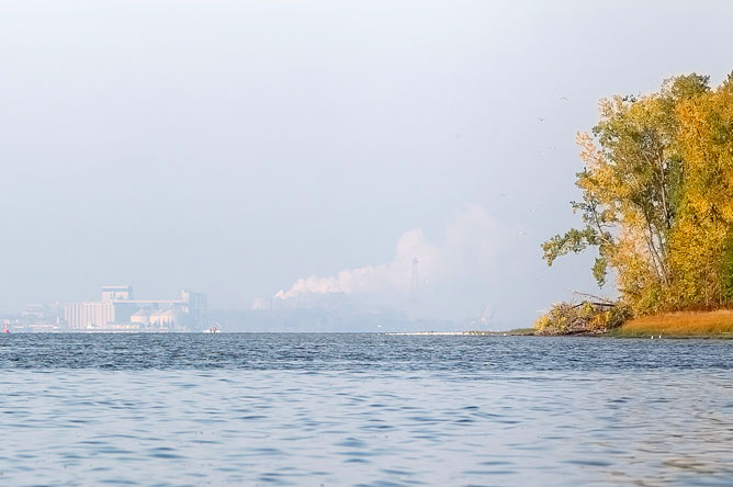 Smokestacks of the factory silhouetted against the horizon, seen from the archipelago.