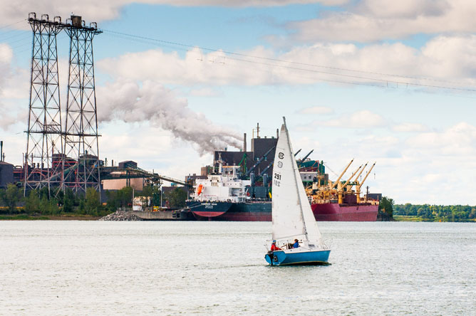 Sailboat on the St. Lawrence and ship moored at the Rio Tinto Fer et Titane wharf on the St. Lawrence.