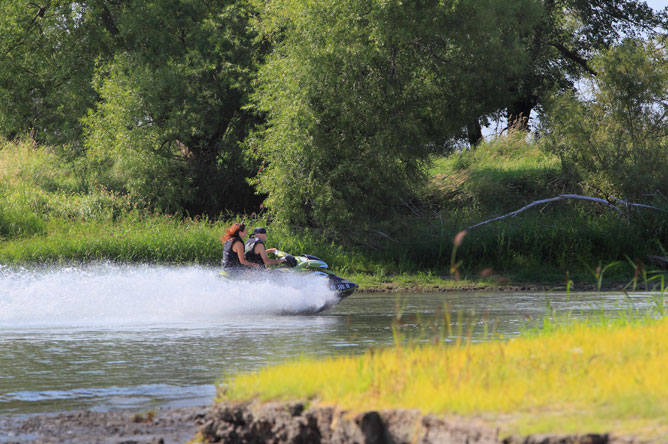 A woman and a man ride a personal watercraft along a channel.