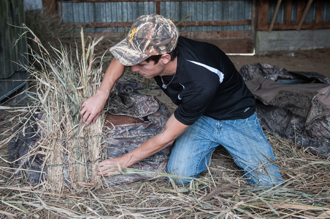 A young man covers a blind in dry vegetation.