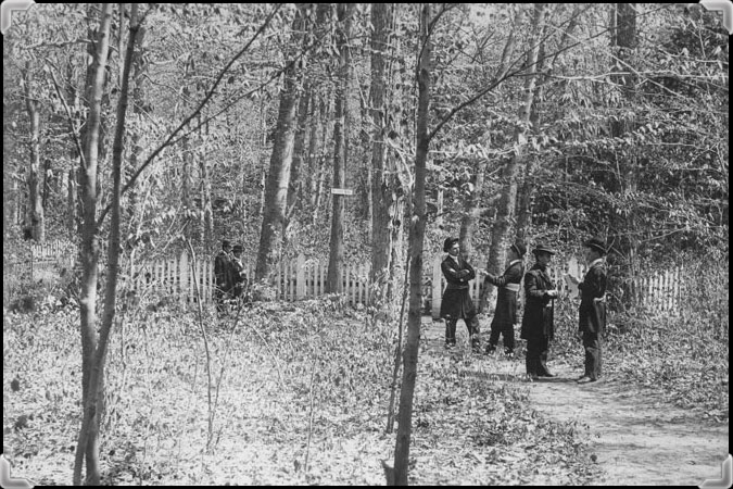 Six men wearing bowler hats and walking in the woodland near the Nicolet Seminary, around 1898.