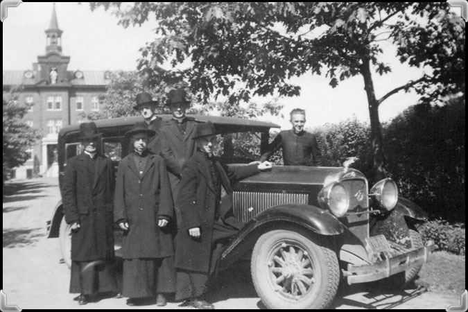 Six men stand near a car in front of the Novitiate of the Montfortain Fathers in Nicolet, 1937.