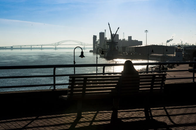 Person seated on a bench facing the St. Lawrence in Trois-Rivières.