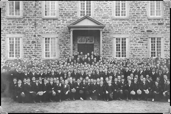 Black and white photograph showing hundreds of students in front of the stone façade of the Seminary of Nicolet.